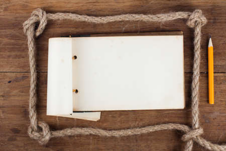 Antique 1943 year Old Grunge Notepad in the Rope Frameon wooden background photo