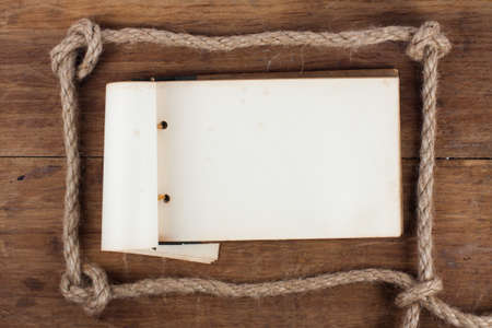 Old Antique 1943 year Grunge Notepad in the Rope Frameon wooden background photo