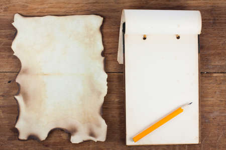 Antique Notepad 1943 year and Burnt Paper on Wood background photo