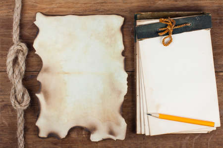 Antique 1943 year Notepad and Burnt Paper on Wood background photo