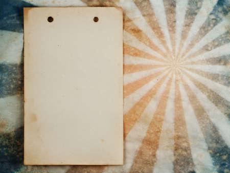 Old notepad sheet on sunburst grunge retro background photo