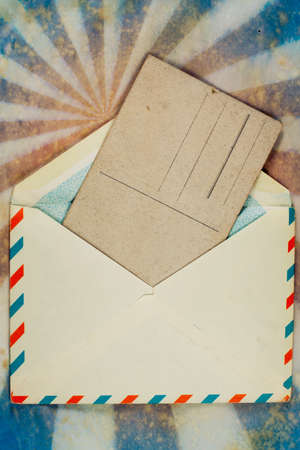 Envelope of Air mail and old postcard on a grunge retro sunburst background photo