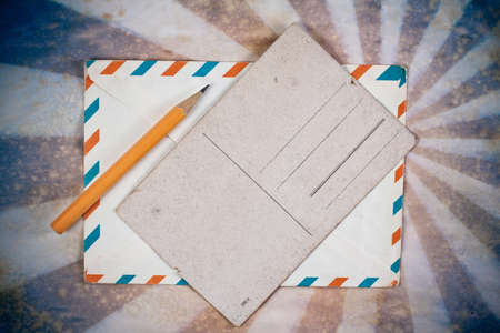 Postcard template, envelope of air mail and pencil on sunburst grunge retro background photo