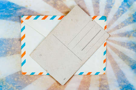 Envelope and old postcard on a grunge retro sunburst background photo