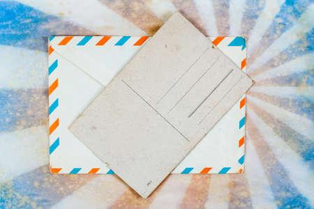 Envelope and old postcard on a grunge retro sunburst background photo