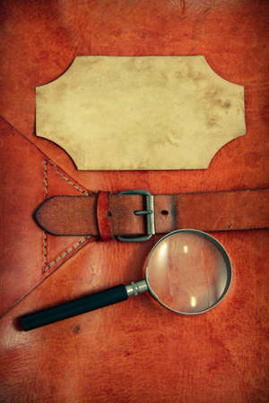 Vintage leather textured background with paper frame and magnifying glass photo