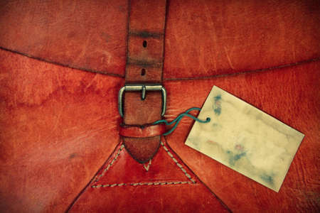 Leather vintage background with a belt and old gift tag photo