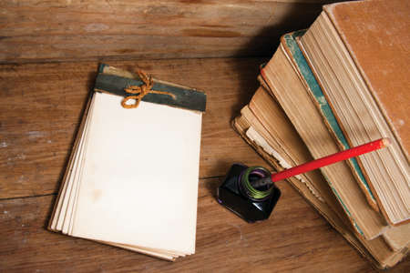 note pad and pen: Antique notebook (1940th), ink pen and inkwell, old books on wood background