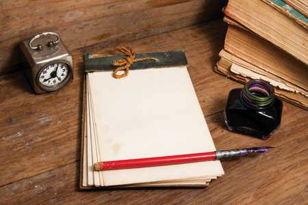note pad and pen: Antique notebook (1940th), vintage clock, ink pen and inkwell, old books on wood background