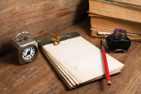 Antique notebook (1940th), vintage clock, ink pen and inkwell, old books on wood background photo