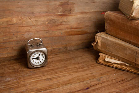 Vintage clock and old books on wood photo