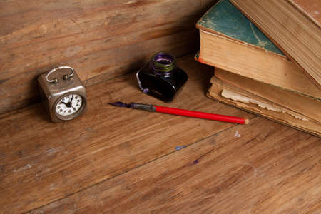 Antique clock, ink pen and inkwell, old books on wood background photo