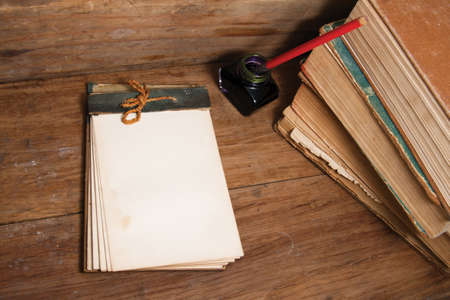 Antique notebook, ink pen and inkwell, old books on wood background photo