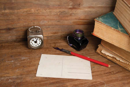 Antique clock, postcard, ink pen and inkwell, old books on wood background photo