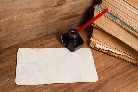 Old grunge paper, books, ink pen and inkwell on wood photo