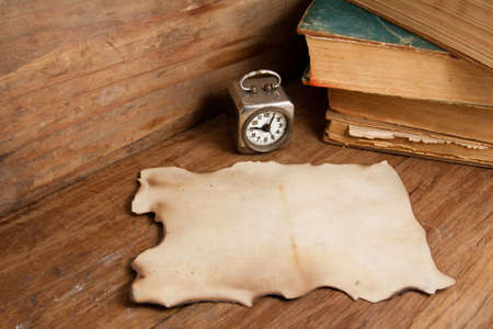Burnt paper, vintage clock, inkwell, pen and old books on wood photo