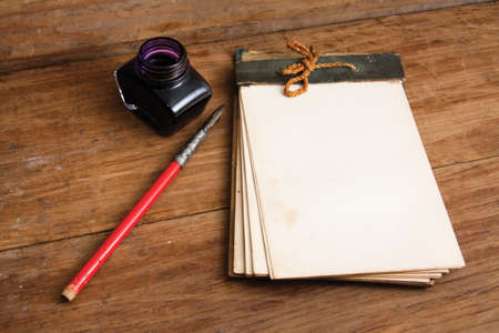 stylus pen: Antique notebook, ink pen and inkwell on wood Stock Photo