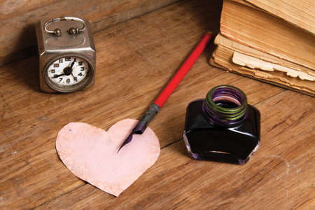 Inkwell, ink pen, heart shape grunge paper, vintage clock, and old books on wood photo