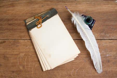 Vecchio taccuino, penna inchiostro della penna e calamaio su sfondo in legno