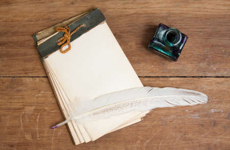 Old notebook, quill ink pen and inkwell on wood background photo