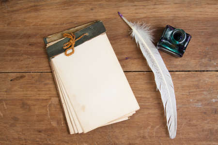 stylus pen: Quill ink pen and inkwell, old notepad on wood table