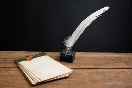 Quill ink pen and inkwell, old notepad on wood table photo