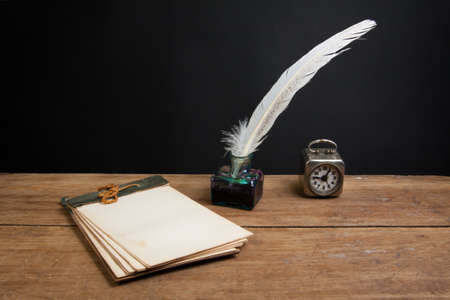 Quill ink pen and inkwell, old notepad, vintage clock on wood table photo