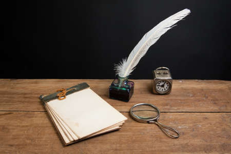 Quill ink pen and inkwell, old notepad, magnifying glass, vintage clock on wood table photo