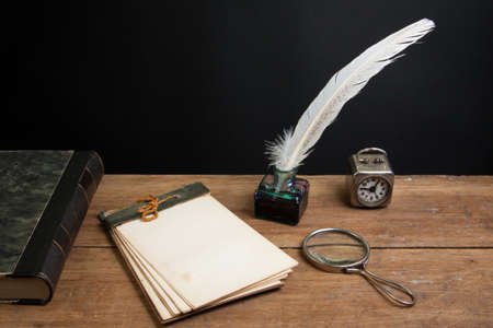 Old notepad, antique book, quill ink pen and inkwell, magnifying glass, vintage clock on wood table photo