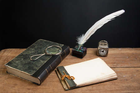 Old notepad, antique book, quill ink pen and inkwell, magnifying glass, vintage clock on wood table Stock Photo - 13010441