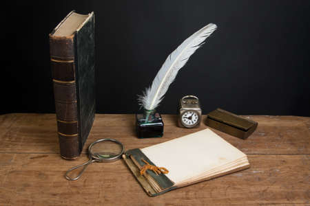 Antique book, magnifying glass, old notepad, quill ink pen and inkwell, vintage clock on wood table photo