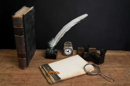 Antique book, magnifying glass, old notepad, quill ink pen and inkwell, vintage binoculars, clock on wood table photo