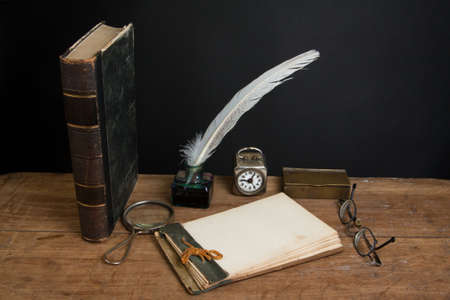 Quill ink pen and inkwell, antique book, magnifying glass, old notepad, vintage spectacles, clock on wood table photo
