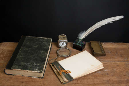 Quill ink pen and inkwell, antique book, magnifying glass, old notepad, vintage clock on wood table photo