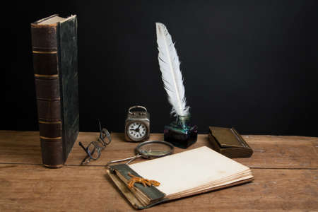 Quill ink pen and inkwell, antique book, magnifying glass, old notepad, vintage clock, spectacles on wood table photo