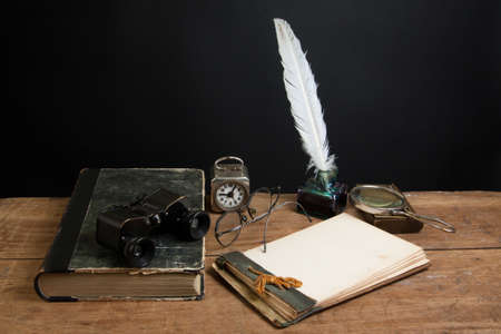 Antique book, binoculars, quill ink pen and inkwell, magnifying glass, old notepad, vintage clock, spectacles on wood table photo
