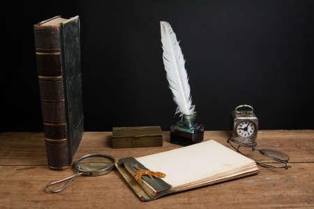 Vecchio taccuino, penna inchiostro della penna e calamaio, lente d'ingrandimento, orologio d'epoca, libri antichi, occhiali sul tavolo in legno