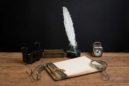Old notepad, quill ink pen and inkwell, binoculars, magnifying glass, vintage clock, spectacles on wood table photo