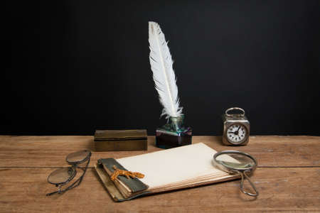 Old notepad, quill ink pen and inkwell, magnifying glass, vintage clock, spectacles on wood table photo