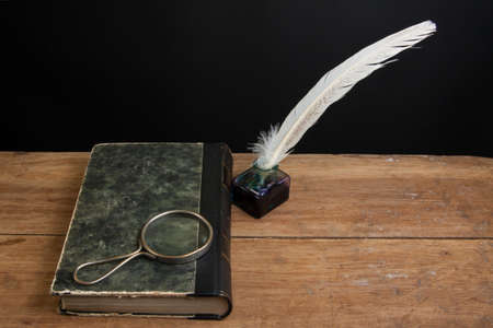 Quill ink pen and inkwell, old book and magnifying glass on wood table Stock Photo - 13010452