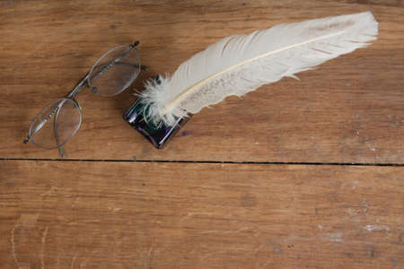 Quill ink pen and inkwell, vintage spectacles on wood table photo