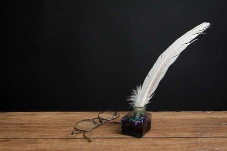 Quill inchiostro della penna e calamaio, gli occhiali d'epoca su tavola di legno