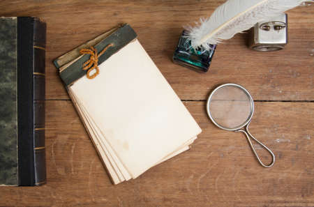 Old notepad, antique book, quill ink pen and inkwell, magnifying glass, vintage clock on wood table Stock Photo - 13010406
