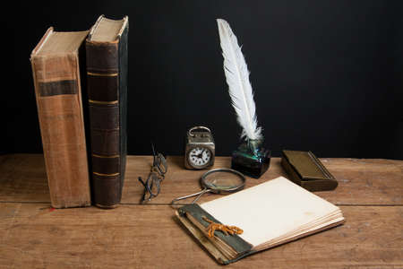 Quill ink pen and inkwell, antique books, magnifying glass, old notepad, vintage clock, spectacles on wood table photo