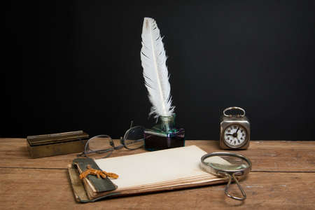 Old notepad, quill ink pen and inkwell, magnifying glass, book, vintage clock, spectacles on wood table photo