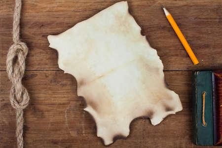 Old verbranntes Papier und Bleistift auf Holzuntergrund