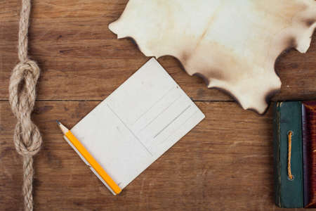 Postcard, pencil and old burnt paper on wooden background Stock Photo - 13010567