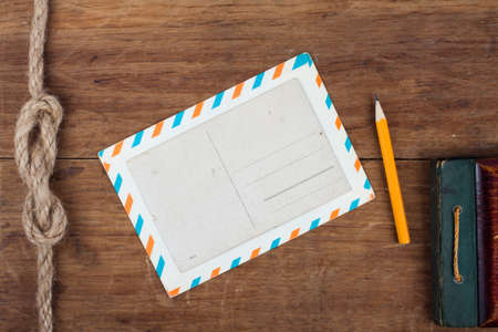 Postcard, envelope, pencil on wooden background Stock Photo - 13010479