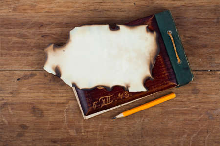Antique Old 1943 year Notepad and Burnt Paper on Wood background Stock Photo - 13010456