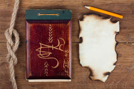 Antique Old 1943 year Notepad and Burnt Paper on Wood background photo